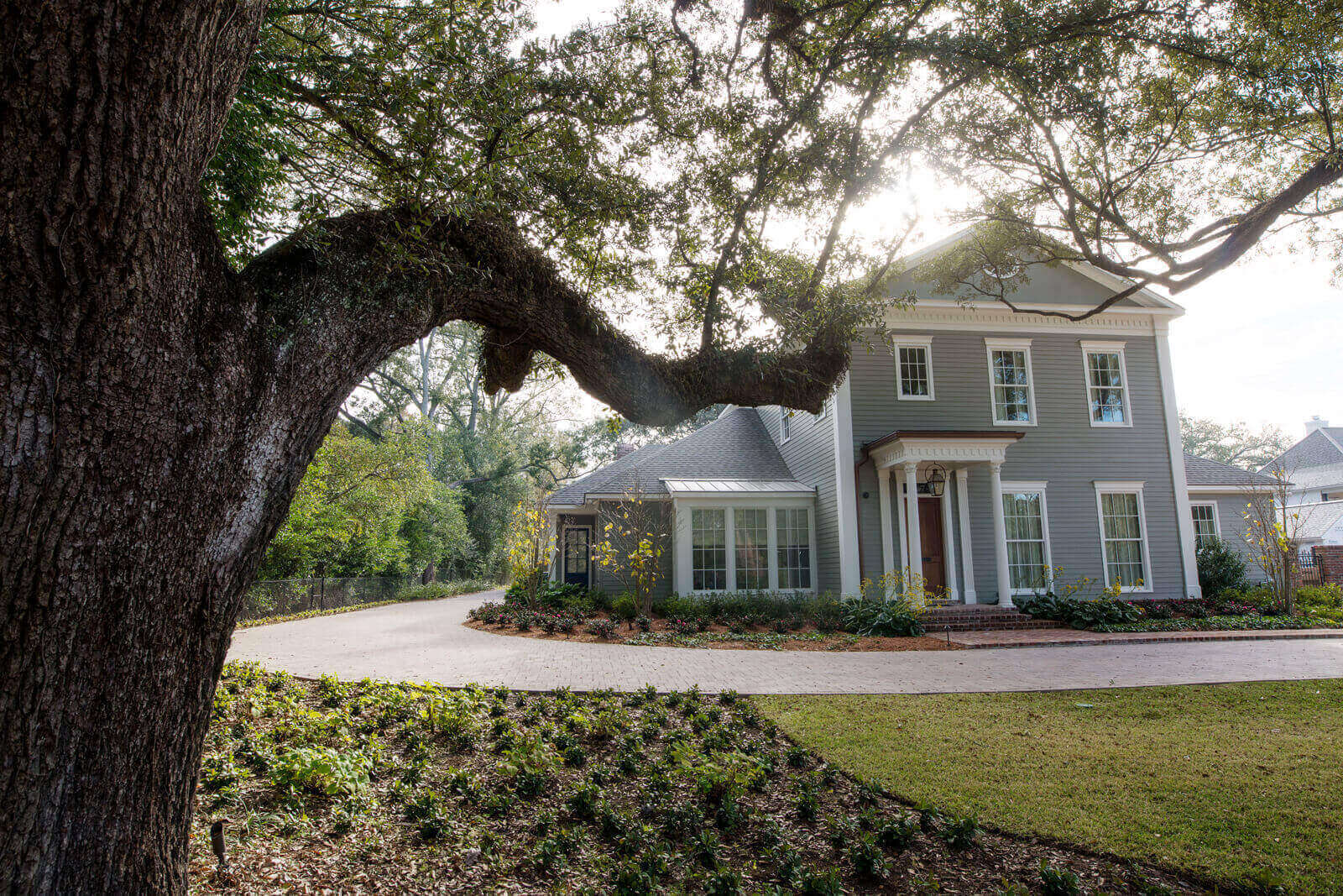 We worked around three historic live oak trees, two retaining walls and challenging slope patterns in conjunction with Montgomery-Waguespack Architecture and Audubon Construction to create a moss-covered, lakeside retreat with sweeping, paved driveways.